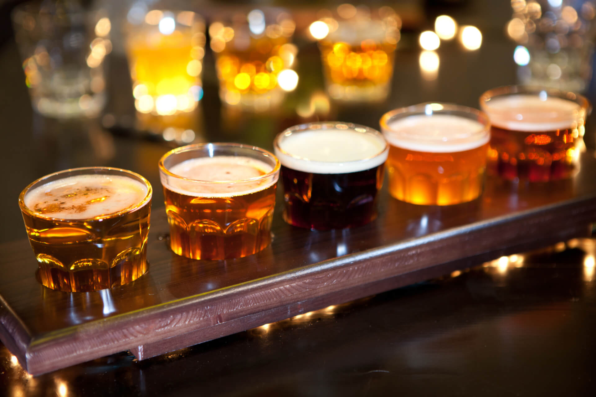 Set of glasses of light and dark beer on a pub background.